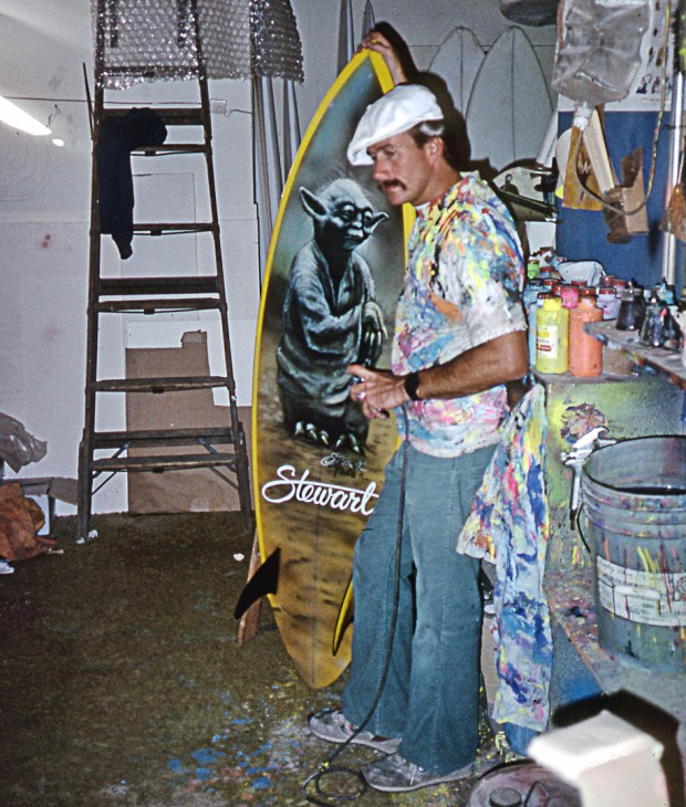 Bill Stewart, surfer, shaper and a pioneer of airbrush art on surfboards, with his early Yoda surfboard.(Courtesy of Friends of San Clemente)