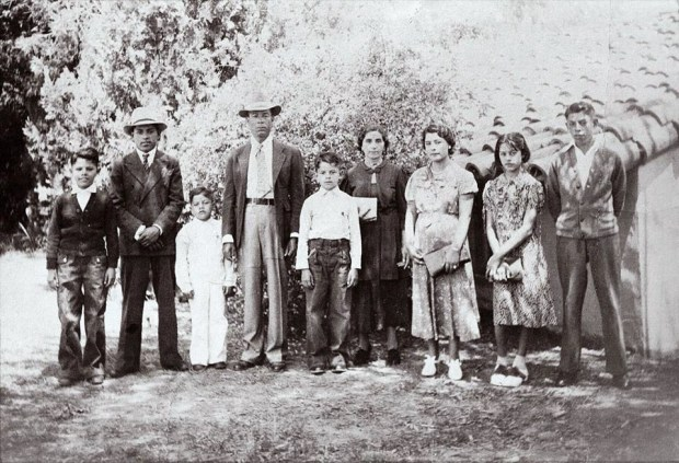 This photo of the Ramirez family, circa 1940, includes Epamuseno Ramirez, fourth from left; wife Mercedes, center; and daughter Eva, second from right, who was about 13. Eva Ramirez Mejia, now 90, wants to know why her sister Elisa s cross no longer sits at her grave in Corona Sunnyslope Cemetery s pauper s graveyard, or Potter s Field, in Corona and believes part of the historic burial ground was sold. (COURTESY OF RAMIREZ MEJIA FAMILY)