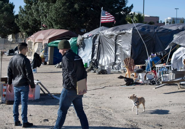 """Encampments like this along the Santa Ana River Trail are targeted for the """"Point-in-Time"""" count and survey of homeless people in Anaheim on Saturday, January 28, 2017. Adam Montague, left, and Will Shaw with 211OC had no luck getting anyone to chat at this site.(Photo by Mindy Schauer, Orange County Register/SCNG)"""