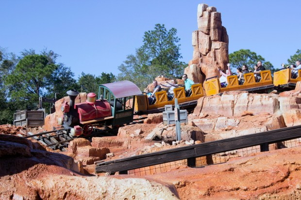 A train full of thrill-seeking riders rounds a bend and down a hill on the Big Thunder Mountain Railroad roller coaster attraction in Frontierland at the Magic Kingdom of Walt Disney World. (Photo by Mark Eades, Orange County Register/SCNG)