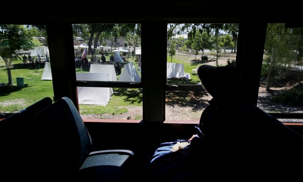 Re-enactor Sarah Bierle of Temecula is silhouetted as she looks out the window at a Civil War basecamp as she rides in a 1920 Delaware, Lackawanna & Western Railways Motor-trailer during a Civil War re-enactment at the Orange Empire Railway Museum in Perris, CA. Sunday, May 21, 2017. TERRY PIERSON,THE PRESS-ENTERPRISE/SCNG