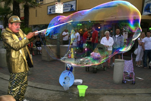 "BIG BUBBLE: Bill Ackroyd ""The Bubble Man"" entertains the crowd on Main Street./// ADDITIONAL INFO: hb.SurfCity.0612- 06/03/08 - Mark Martinez / The Register Shots of street performers at Surf City Nights in Huntington Beach."