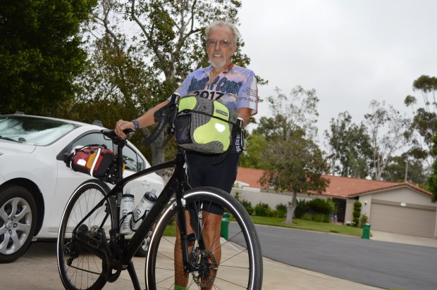Outside his home in Laguna Woods, Phil Foreman wears his jersey from the coast-to-coast bicycle trip he took earlier this year. (Photo by Emily Rasmussen, contributing photographer)