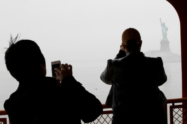 Passengers on the Staten Island ferry photographer the Statue of Liberty shrouded in heavy fog, Thursday, Feb. 23, 2017 photo, in the New York harbor. (AP Photo/Mary Altaffer)
