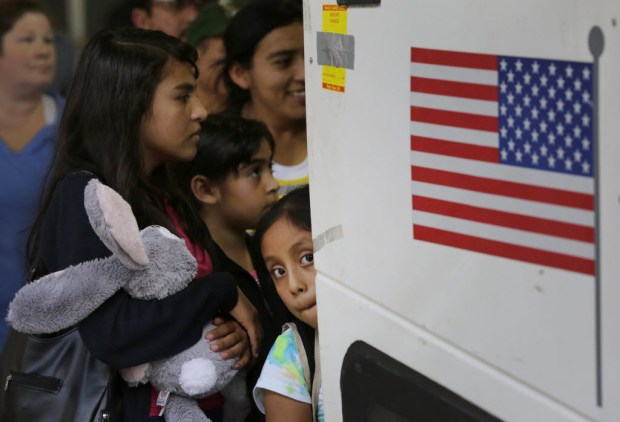 Immigrants from El Salvador and Guatemala who entered the country illegally board a bus July 7, 2015, after they were released from a family detention center in San Antonio. Many of the children were unaccompanied by an adult. (Eric Gay, The Associated Press)