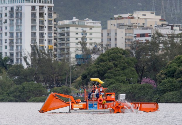 Crews skim the water surface for trash and debris at the Rodrigo de Freitas Lagoon in Rio de Janeiro in July 2016 before the start of the Olympic Games. (File photo by MICHAEL GOULDING, The ORANGE COUNTY REGISTER/SCNG)
