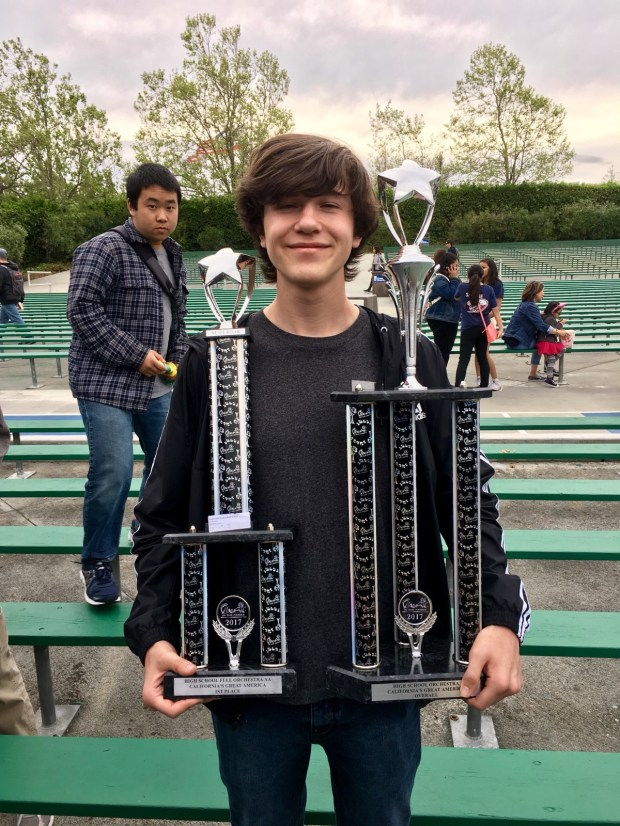 Sean Lovullo holds awards won by the orchestra of Capistrano Valley High School at a festival in San Francisco during a trip to the Bay Area in April 2017. (Photo courtesy of Capistrano Valley High School)