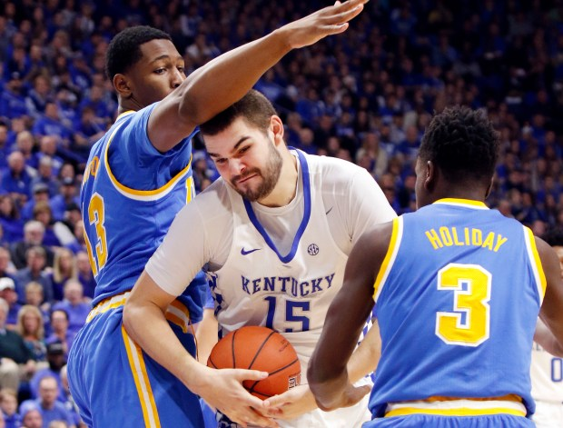 Kentucky's Isaac Humphries looks for an opening between UCLA's Ike Anigbogu, left, and Aaron Holiday during their December meeting in Lexington, Ky. Humphries was one of six players who participated in a pre-draft workout for the Lakers on Monday in El Segundo. (AP Photo/James Crisp)