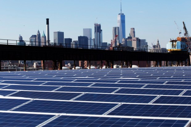 In this Feb. 14, 2017 photo, a rooftop is covered with solar panels at the Brooklyn Navy Yard in New York. The Manhattan skyline is at top. Even if President Donald Trump withdraws U.S. support for the Paris climate change accord, domestic efforts to battle global warming will continue. Dozens of states and many cities have policies intended to reduce emissions of greenhouses gases and deal with the effects of rising temperatures. Even in red states, many consider flood prevention and renewable energy are considered smart business. (AP Photo/Mark Lennihan) ORG XMIT: CER202