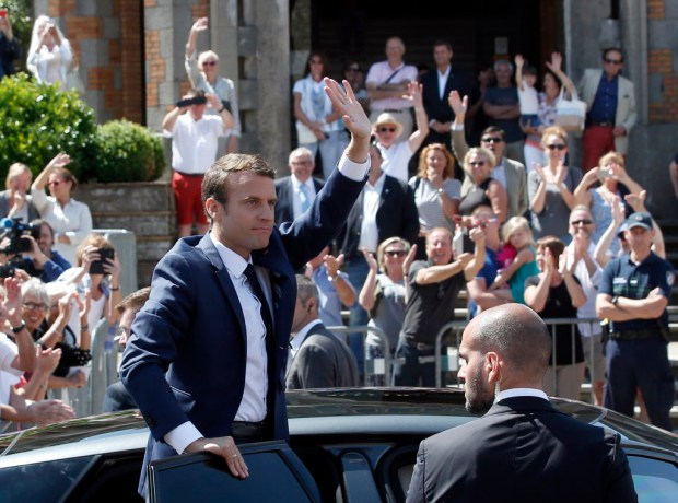 "French President Emmanuel Macron waves to the audience as he leaves a polling station in Le Touquet, northern France, after casting his vote in the first round of the two-stage legislative elections, Sunday, June 11, 2017. French voters are choosing legislators in the first round of parliamentary elections, with President Emmanuel Macron's party ""Republic on the Move"" hoping to win a strong majority in the National Assembly to push through bold labor and security reforms. (AP Photo/Thibault Camus)"