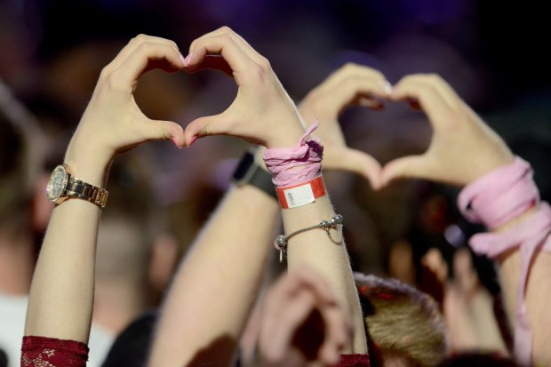 In this Sunday, June 4, 2017, handout photo provided by Dave Hogan for One Love Manchester, fans make heart shapes from their hands at the One Love Manchester tribute concert in Manchester, north western England, Sunday, June 4, 2017. One Love Manchester is raising money for those affected by the bombing at the end of Ariana Grande's concert in Manchester on May 22, 2017. (Dave Hogan via AP) ORG XMIT: LENT141