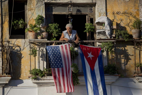 In this Dec. 19, 2014 file photo, Javier Yanez stands on his balcony decorated with U.S. and Cuban flags in Old Havana, Cuba. On Friday, June 16, President Donald Trump turned America's Cuba policy on its second 180-degree spin in three years. Ordinary Cubans are bracing for the worst. (AP Photo/Ramon Espinosa, File)