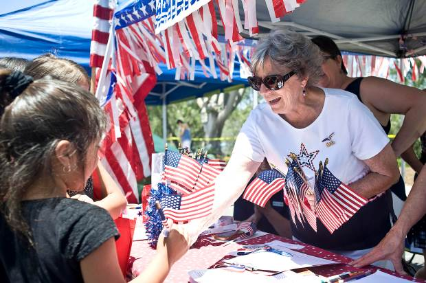 Bunny Smith of the Daughters of the American Revolution passes out flags for answering questions about American history during Mission Viejo's annual Fourth of July Street Faire in 2016. (File photo by Nick Agro, Orange County Register/SCNG)
