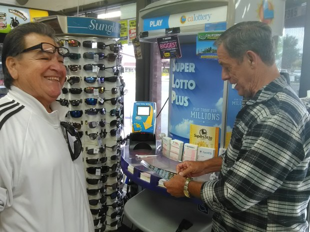 Jesus Cosio, left, talks to his friend Dean Castle, who plays a lottery game at Marietta Liquor and Deli in Menifee on Sunday, June 11. The store sold a Powerball ticket that won more than $477 million in Saturday night's drawing. (Photo by Stephen Wall, The Press-Enterprise/SCNG)