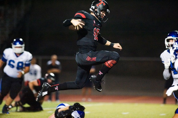 San Clemente quarterback Sam Darnold leaps over a Dana Hills player to score a touchdown at San Clemente High School on Friday ///ADDITIONAL INFORMATION: hspercy.0913 Ð 9/12/14 Ð FOSTER SNELL, ORANGE COUNTY REGISTER - Dana Hills at San Clemente. Boys varsity football.