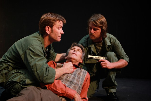 """In """"The Old Man in the Cave,"""" Major French (Michael J. Keeney, left) and Lt. Furman (James A. Manke) threaten Goldsmith (Glenn Freeze) with violence, challenging his assertions that an unseen presence has kept a group of nuclear holocaust survivors safe for 10 years. (Photo by Kirk Schenck Huff)"""