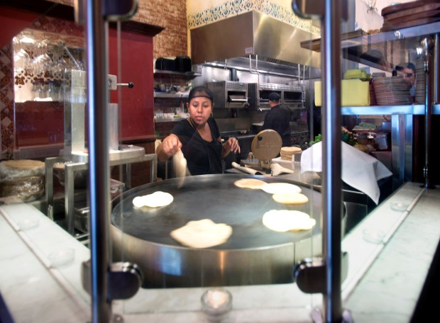 Staffer Madai Villa presses and places homemade corn tortillas on a rotating grill at Gabbi's Mexican Kitchen in Orange. (File photo by Cindy Yamanaka, Orange County Register/SCNG)