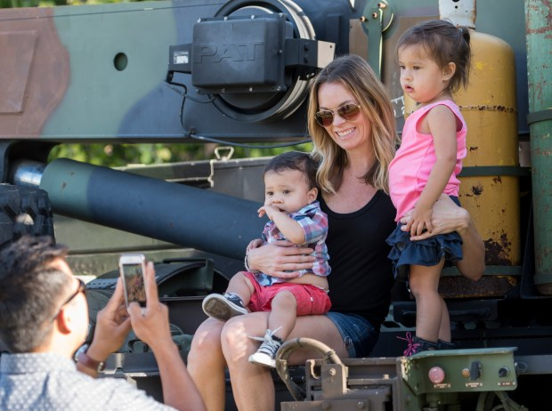 Vernan Ibong, left, of Aliso Viejo takes a photo of his family, from left, son Brock, 1, wife Amanda and daughter Presley, 2, as they sit on a USMC AMK 36 truck, from the 1st Maintenance Battalion at Camp Pendleton during the National Night Out event at Grand Park in Aliso Viejo on Friday, July 21, 2017 (Photo by Leonard Ortiz, Orange County Register/SCNG)