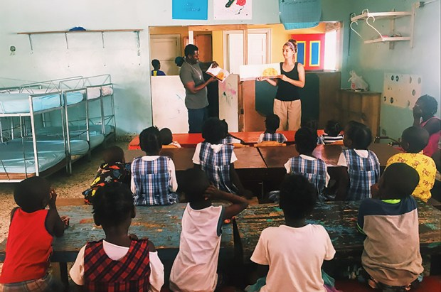 Cal State Fullerton student Lindsey Hass gives a literacy lesson to Haitian preschool children during her teacher training abroad this summer. (Photo courtesy of Cal State Fullerton)