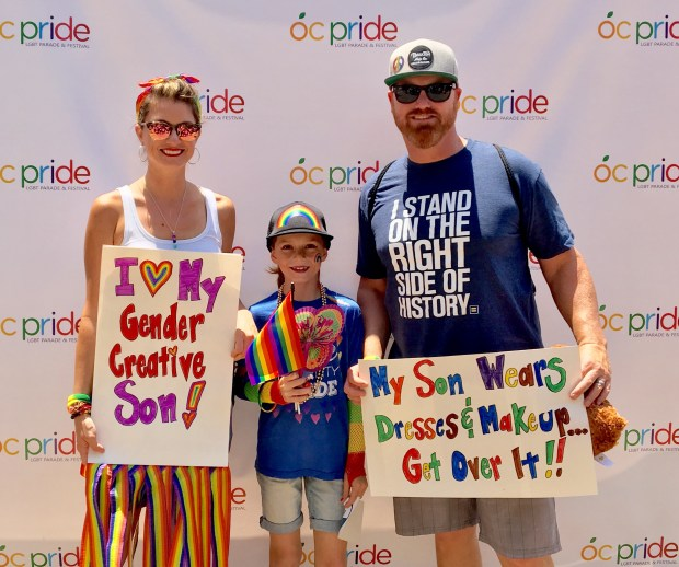 Lori, C.J. and Matt Duron hold signs and a rainbow flag as they attend OC Pride on June 24 in Santa Ana. The Orange County family was criticized by actor James Woods and others on Twitter. (Photo courtesy of Lori Duron, Raising my Rainbow)