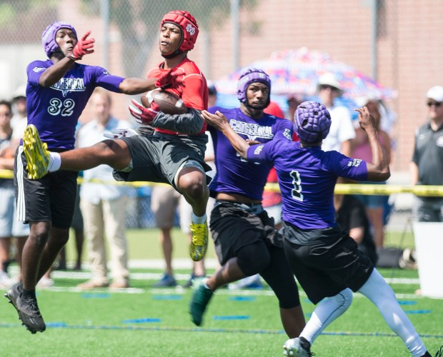 Mater Dei wide receiver CJ Parks reels in a one-handed catch between three Cathedral defenders during the Battle at the Beach seven on seven football tournament at Edison High School in Huntington Beach on Saturday, July 8, 2017. (Photo by Matt Masin, Orange County Register, SCNG)
