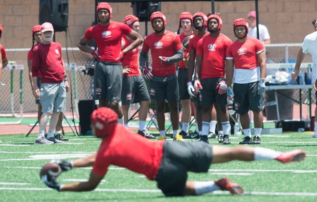 Mater Dei bench players watch as a teammate intercepts a Servite pass during the Battle at the Beach seven on seven football tournament at Edison High School in Huntington Beach on Saturday, July 8, 2017. (Photo by Matt Masin, Orange County Register, SCNG)