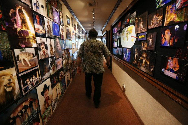 Garner Holt of Garner Holt Productions, who specializes in animatronics, walks the halls of his San Bernardino location filled with photos of his work. (Stan Lim, The Press-Enterprise/SCNG)