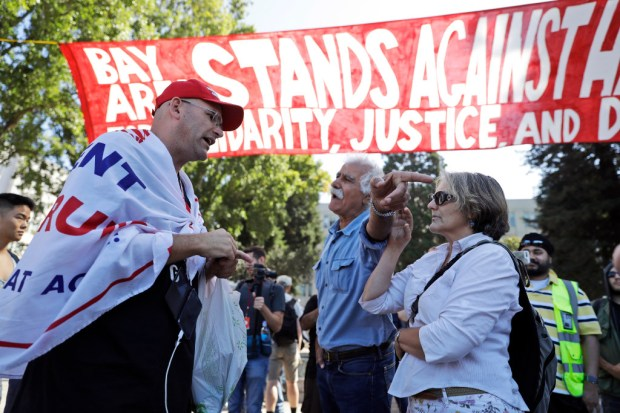 "Donald Trump supporter Arthur Schaper, left, argues his position with Mustafa Payrvand, center, and Christina Tunnah during a free speech rally Aug. 27 in Berkeley. Protesters gathered for a ""Rally Against Hate"" in response to a planned right-wing protest. (Marcio Jose Sanchez, The Associated Press)"