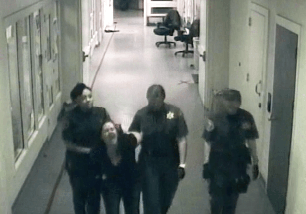 Alison Boroch filed a lawsuit against Orange County in December alleging mistreatment by OC Sheriff's Deputies Olivia Coco and Terra Carrillo, who are flanking her. Brooch alleges deputies injured her arm during her booking. (OCSD security camera video)