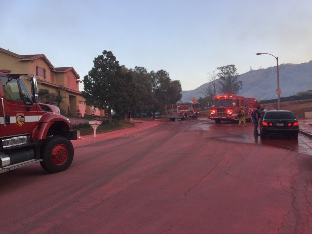 Homes and the roadway on Alta Brisa Way in Moreno Valley are painted a pinkish red from fire retardant dropped by tankers fighting the Blaine fire in the nearby Box Springs Mountains on Sunday, Aug. 13, 2017. (Photo courtesy of Mike Beebe)