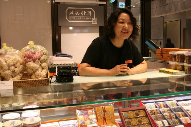 Gyodong sells traditional Korean delicacies packaged in fancy gift boxes or purchased a la carte. Gui Eun Lee, Gyodong's sales manager, provides samples of fried pastries and sticky rice confections.