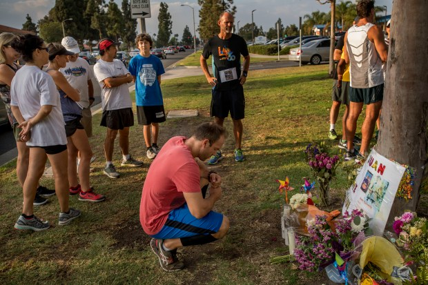 Runner Cole Gatchell, center, of Irvine pays his respects at a memorial for Juan Ramirez in Fountain Valley on Thursday, August 31, 2017. Runners gathered a Mile Square Park for a memorial run in honor of Ramirez who was killed by a hit and run driver along Brookhurst St. recently. (Photo by Paul Rodriguez, Orange County Register/SCNG)