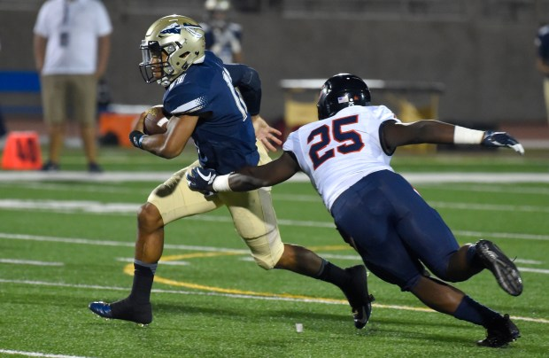 Bosco QB Re-al Mitchell escapes Chaminade's Jonathan Thomas's grasp in Torrance on Friday, September 8, 2017. St. John Bosco vs Chaminade preseason football game at El Camino College. (Photo by Scott Varley, Press-Telegram/SCNG)