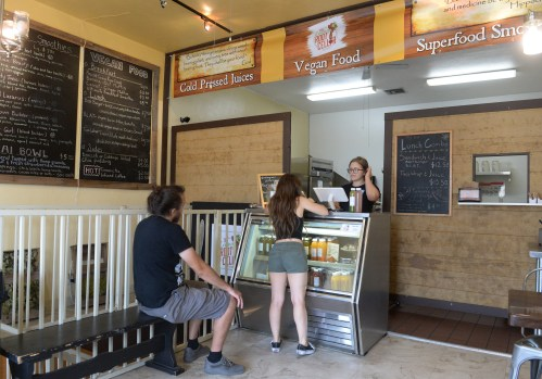 Madeleine Faulk helps a customer at The Living Root Cellar in downtown Redlands, Tuesday, Sept. 12, 2017. The business specializes in cold-pressed juices, along with vegan food, smoothies and desserts. New owners Sam and Ashleigh Benavides purchased The Living Root Cellar earlier this year and are celebrating the grand reopening from Sept. 10-29, 2017. (Photo by John Valenzuela/Redlands Daily Facts/SCNG)