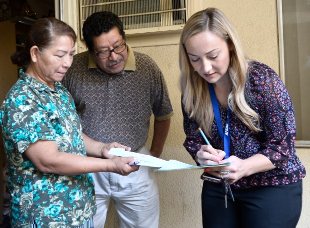 Mercedes and Joaquine Calles, left, get information from Megan Brown, an attendance counselor with the Los Angeles Unified School District. The Calles grandson was living with them, but moved out of town to work in the agricultural industry, and dropped out of school.