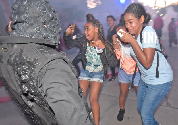 "Park visitors are accosted by one of the 500 ""scareacters""on hand at the Six Flags Fright Fest Opening Night at Six Flags Magic Mountain in Valencia on Saturday, Sept. 16, 2017. (By Dan Watson. Contributing Photographer, Los Angeles Daily News/SCNG)"