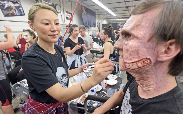 "Jo Jo Zhu, left, joins 42 other makeup artist as she puts the finishing touches to Jacob Lucero, one of 500 ""scareacters"" on hand at the Six Flags Fright Fest Opening Night at Six Flags Magic Mountain in Valencia on Saturday evening. Saturday, Sept. 16, 2017. (By Dan Watson. Contributing Photographer, Los Angeles Daily News/SCNG)"