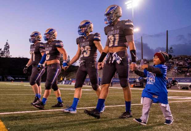 Joshua Esquivel, 5, walks onto the field with Santa Margarita players as the honorary team captain for the football team's game against Mission Viejo in Mission Viejo on Friday, September 22, 2017. Joshua fought a grade 4 brain tumor called pineoblastoma. (Photo by Paul Rodriguez, Orange County Register/SCNG)