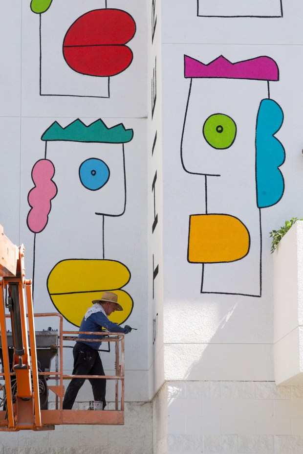 Mural artist Thierry Noir puts finishing touches on his work on The Lofts at NoHo. Noir, a French artist, is most widely known for his art on the Berlin Wall, featuring his trademark cartoon-like characters. (Photo by David Crane, Los Angeles Daily News/SCNG)