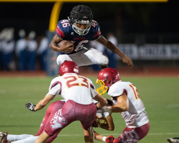 Yorba Linda running back Jonah Slack jumps over El Modena defenders in the second quarter of a non-league football game at Yorba Linda High Friday night September 29, 2017. (Photo by Sam Gangwer, Orange County Register/SCNG)