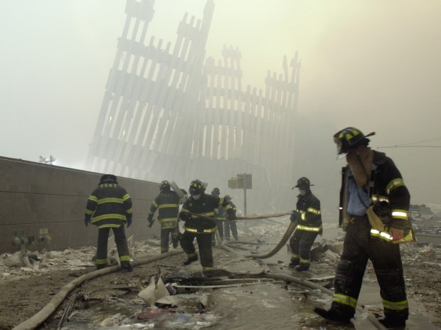 FILE - In this Sept. 11, 2001 file photo, firefighters work beneath the destroyed mullions, the vertical struts which once faced the soaring outer walls of the World Trade Center towers, after a terrorist attack on the twin towers in New York. (AP Photo/Mark Lennihan)