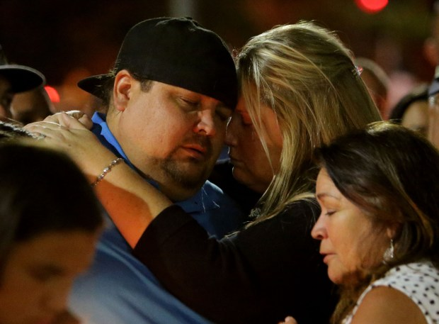 Jonathan Mulligan, 36, of Chino Hills and his wife, Elizabeth, attended the concert with friends Rocio Rocha Guillen, 40, and her fiancŽe, Chris Jaksha. The Mulligans comfort one another during a candlelight vigil at Roosevelt High School Thursday, Oct. 5 in Eastvale. (Photo by Terry Pierson, The Press-Enterprise/SCNG)