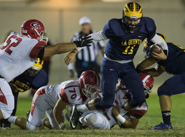 La Quinta quarterback Michael Nadeau is brought down by Garden Grove's Nathan Tran, Andrew Rio and Cristian Marquez during the first half of their Garden Grove League game at Bolsa Grande High in Garden Grove, CA on Thursday, October 5, 2017. (Photo by Kevin Sullivan, Orange County Register/SCNG)