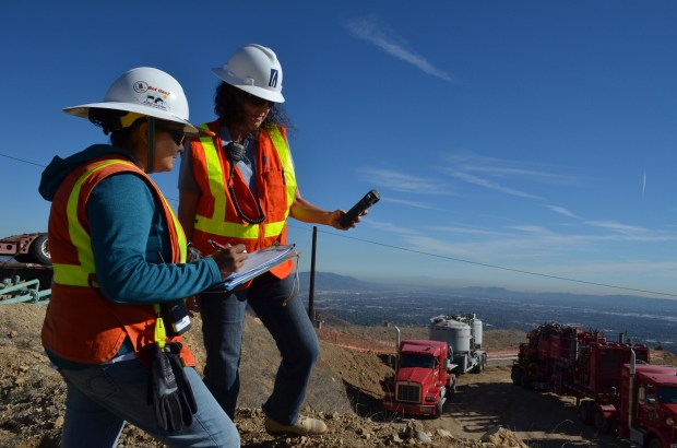 Certified industrial hygienists Sonia Rodriguez (L) and Bonnie Feemster take air samples to measure methane levels at the work site where SoCalGas crews have set up equipment as they work to safely stop the flow of gas at a leaking natural gas storage well at the Aliso Canyon facility in the mountains above Northridge, CA. on November 20, 2015. (Photo courtesy SoCalGas)