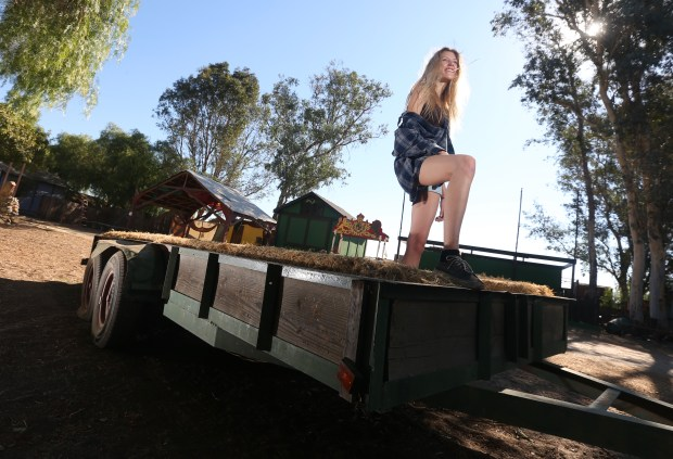 "Kassidy Casey stands on a trailer used for hay rides through ""The Village"" at Coffin Creek in Corona. The Halloween attraction will offer a family friend afternoon for Halloween. (Stan Lim, The Press-Enterprise/SCNG)"