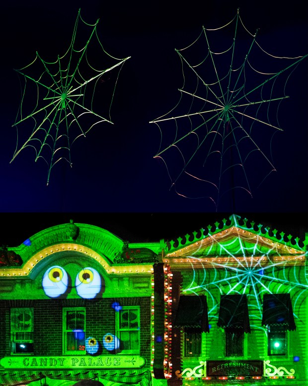 Purple spider webs are projected on Disneyland's Main Street U.S.A., below, but a contrasting green ones scare at Disney California Adventure's Cars Land on Mon., Oct. 30. (Photo by Cindy Yamanaka, Orange County Register/SCNG)