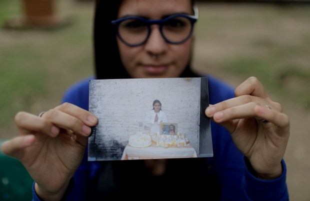 In this Oct. 11, 2017 photo, Karen Maydana, 22, shows a picture of herself as a child celebrating her first Holy Communion in Caseros, in the province of Buenos Aires, Argentina. Maydana says she was 9 years old when the Rev. Carlos Jose fondled her at a church pew facing the altar on the day of her first confession ahead of her first Holy Communion. (AP Photo/Natacha Pisarenko)
