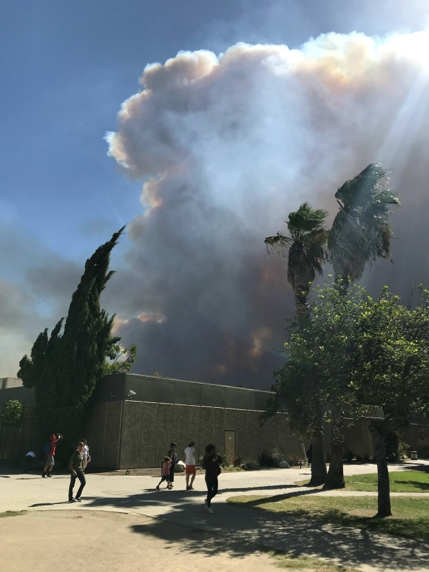 Smoke towers above Canyon High on Monday from the nearby Canyon Fire 2, which forces Canyon and other Orange Unified School District schools to suspend all afternoon sports.