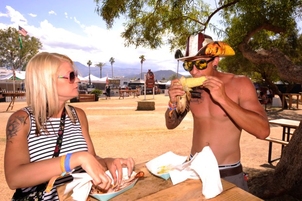 Troy Graham, right, 28, of San Jacinto, eats barbeque corn while Maria Nolde, 28, of San Jacinto, east barbeque chicken during the Stagecoach Country Music Festival in Indio on Sunday, May 1, 2016. (Photo by Rodrigo Pena for the Southern California News Group)