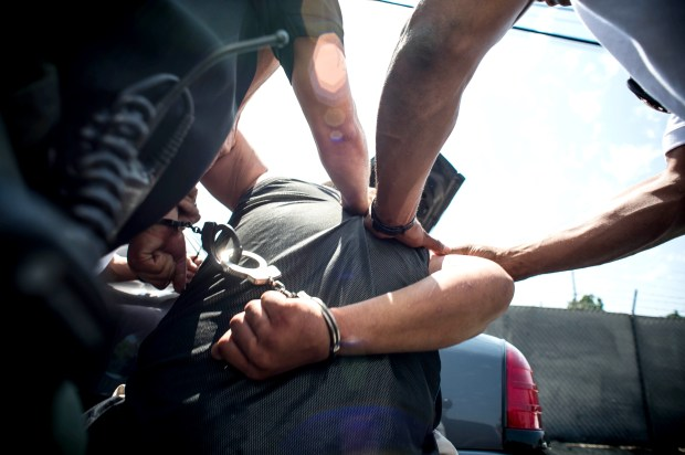 A MET team assists a LASD deputy with a man, whose mother says he was off his meds, in Norwalk. He resisted being moved from a patrol vehicle to an unmarked car and had to be restrained and transported by paramedics for a psych hold. (Photo by Sarah Reingewirtz, Los Angeles Daily News/SCNG)